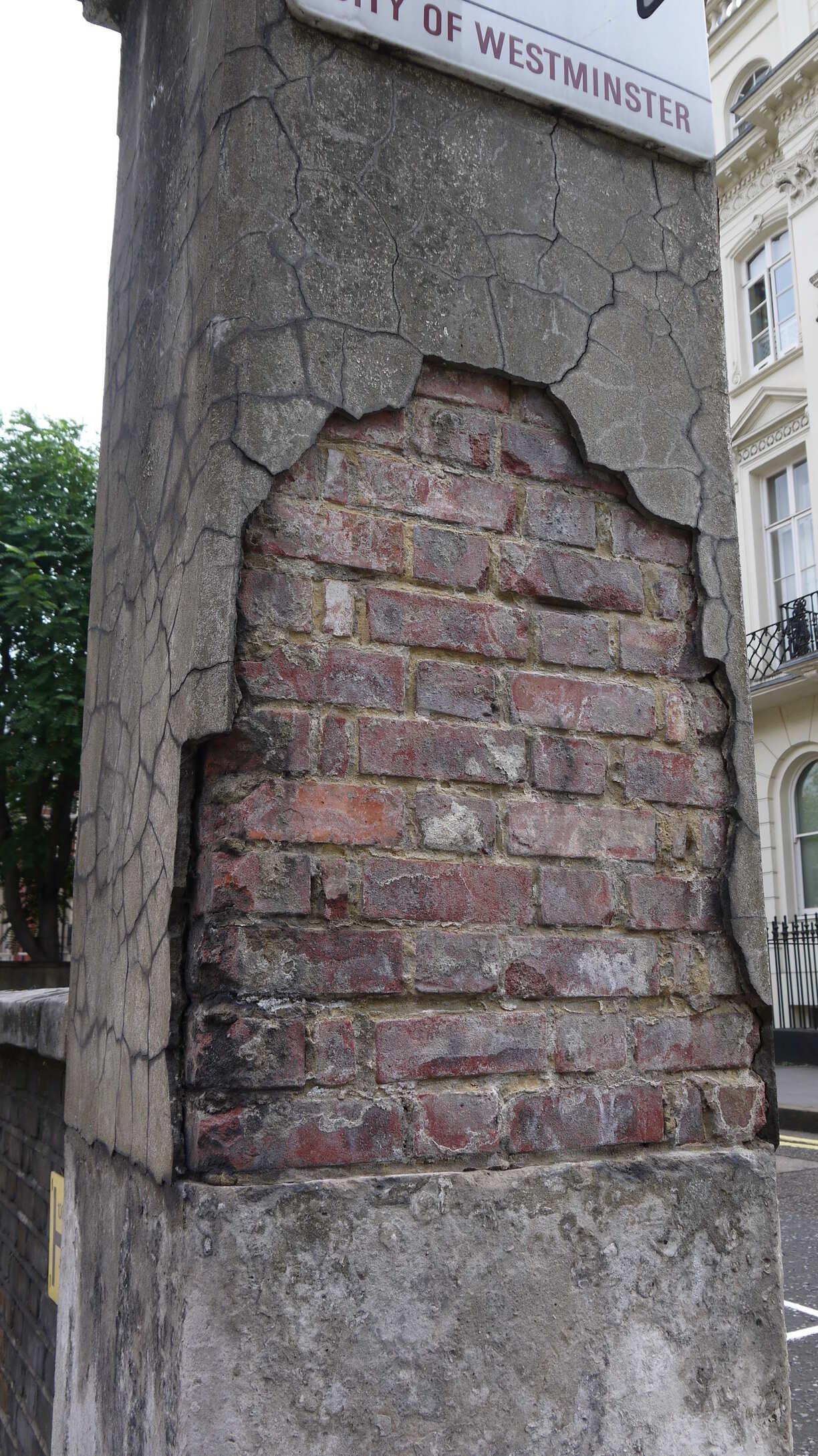 Mur bétonné laissant apparaitre ses briques.