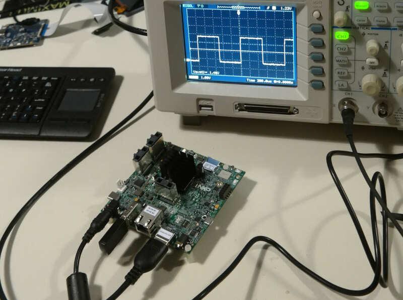 Photographie d'une dev board reliée à un oscilloscope.