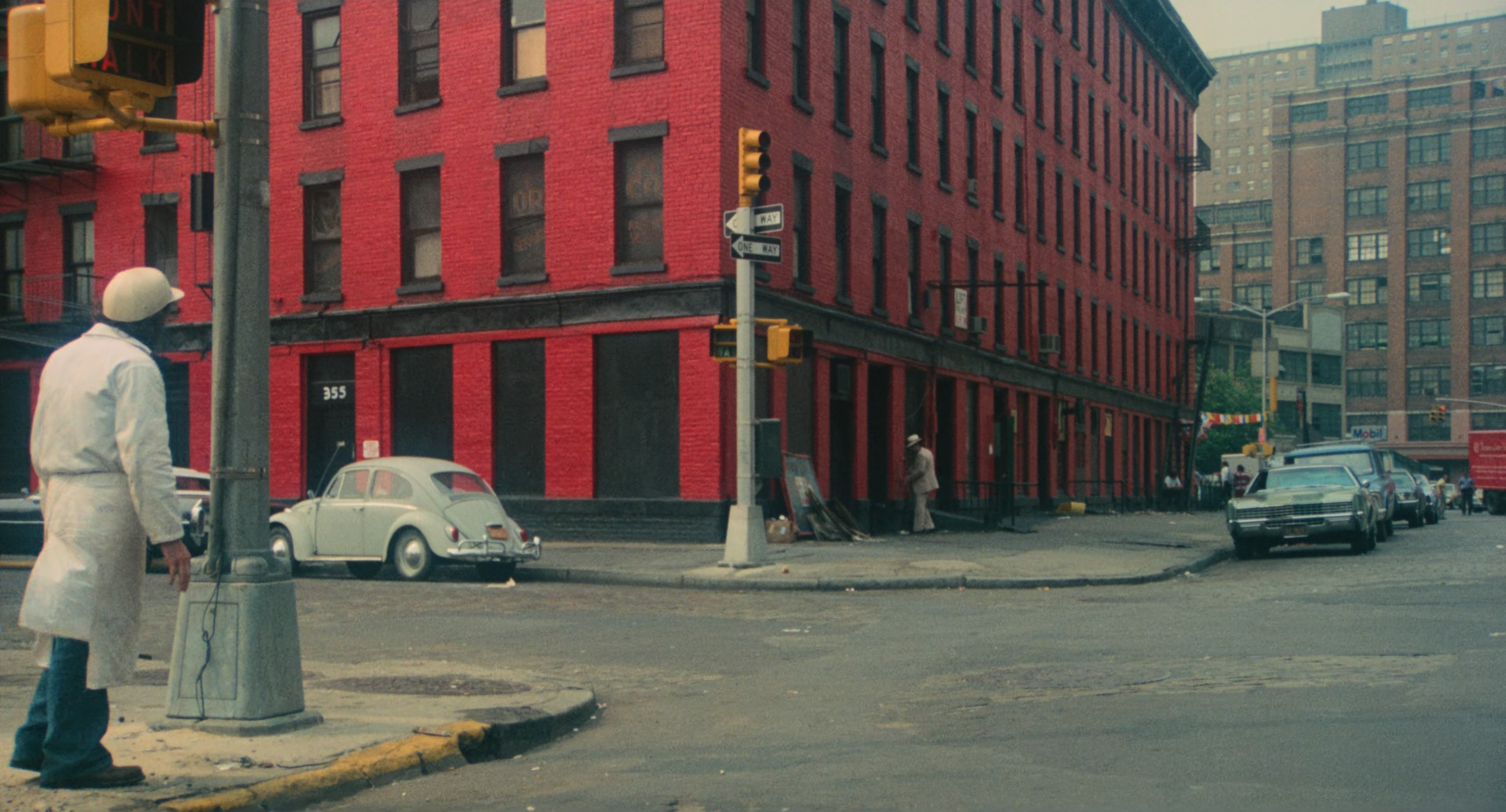 extrait du milieu du film avec le héros tout à gauche du plan, un bâtiment rouge vif au milieu, la rue à droite avec une perspective qui en jette